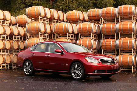 AUT 41 RK0196 01 © Kimball Stock 2006 Infiniti M45 Red 3/4 Side View On Pavement By Barrels