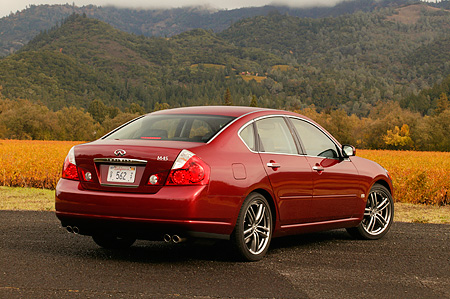 AUT 41 RK0229 01 © Kimball Stock 2006 Infiniti M45 Red 3/4 Rear View On Pavement Hills And Trees Background