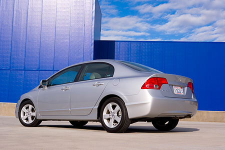 AUT 41 RK0448 01 © Kimball Stock 2006 Honda Civic EX Silver Low 3/4 Rear View On Pavement By Building