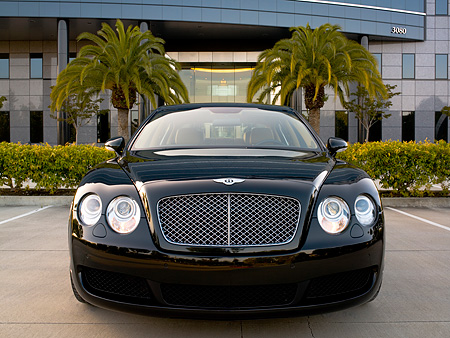AUT 41 RK0473 01 © Kimball Stock 2006 Bentley Continental Flying Spur Black Head On View On Pavement By Building And Trees