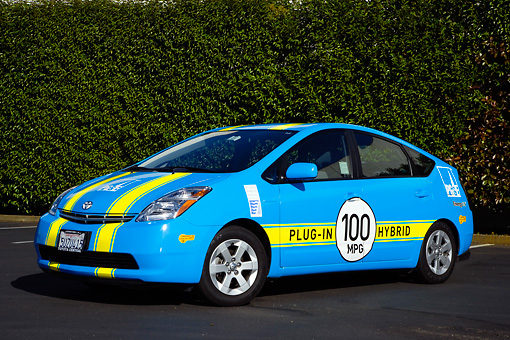 AUT 41 RK0551 01 © Kimball Stock 2006 Toyota Prius Plug-In Hybrid Blue With Yellow Stripes 3/4 Front View On Pavement By Shrubs