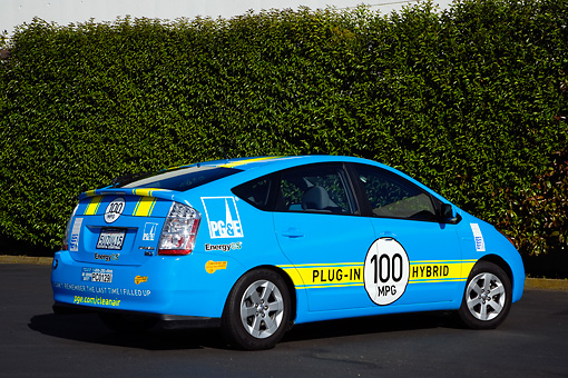 AUT 41 RK0552 01 © Kimball Stock 2006 Toyota Prius Plug-In Hybrid Blue With Yellow Stripes 3/4 Rear View On Pavement By Shrubs