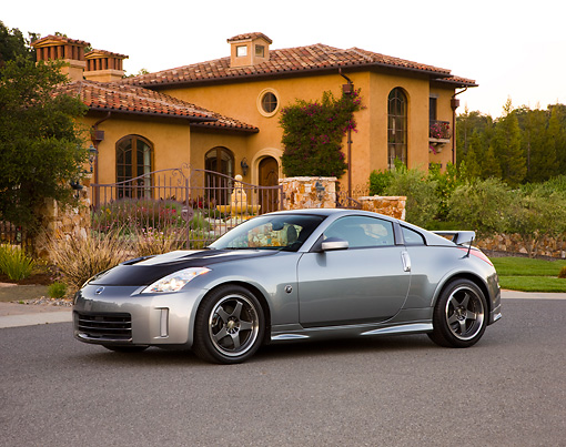 AUT 41 RK0572 01 © Kimball Stock 2006 Nissan 350Z Silver 3/4 Front View On Pavement By House