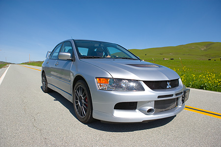 AUT 42 RK0013 01 © Kimball Stock 2007 Mitsubishi Lancer Evolution Silver 3/4 Front View On Road By Grass Hills