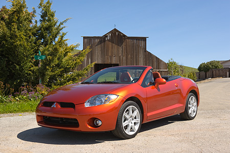 AUT 42 RK0014 01 © Kimball Stock 2007 Mitsubishi Eclipse Spyder Orange 3/4 Front View On Pavement By Barn