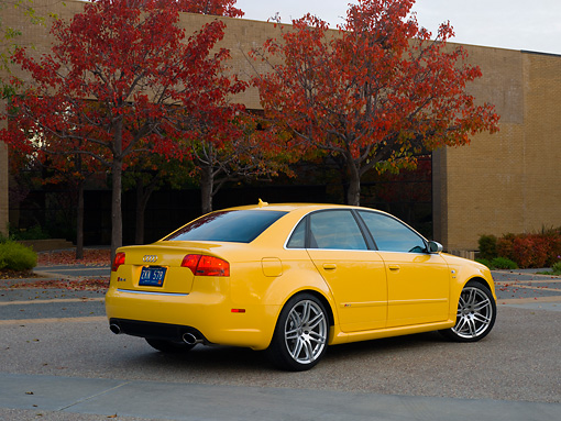AUT 42 RK0111 01 © Kimball Stock 2007 Audi RS4 Yellow 3/4 Rear View On Pavement By Building And Fall Trees
