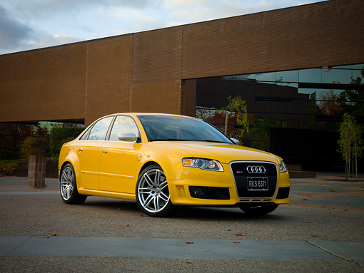 AUT 42 RK0114 01 © Kimball Stock 2007 Audi RS4 Yellow 3/4 Low Front View On Pavement By Building