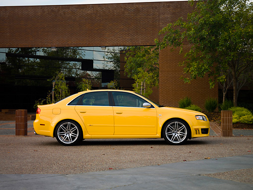 AUT 42 RK0115 01 © Kimball Stock 2007 Audi RS4 Yellow Low Profile View On Pavement By Building