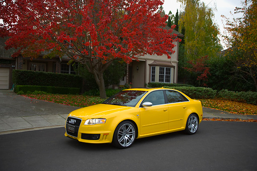 AUT 42 RK0117 01 © Kimball Stock 2007 Audi RS4 Yellow 3/4 Side View On Pavement By House