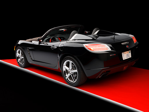AUT 42 RK0136 02 © Kimball Stock 2007 Saturn Sky Turbo Convertible Black 3/4 Rear View On Red Floor Studio