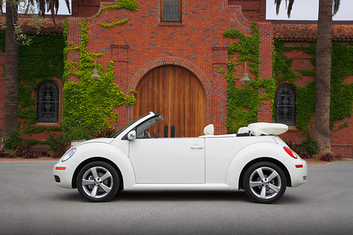 AUT 42 RK0217 01 © Kimball Stock 2007 Volkswagen New Beetle Convertible White Profile View On Pavement By Brick Building