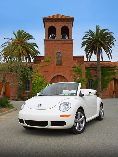 AUT 42 RK0220 01 © Kimball Stock 2007 Volkswagen New Beetle Convertible White 3/4 Front View On Pavement By Tower