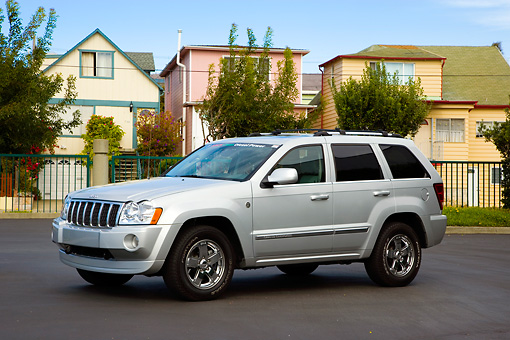 AUT 42 RK0266 01 © Kimball Stock 2007 Jeep Grand Cherokee Overland Silver 3/4 Front View On Pavement By Houses Trees Blue Sky