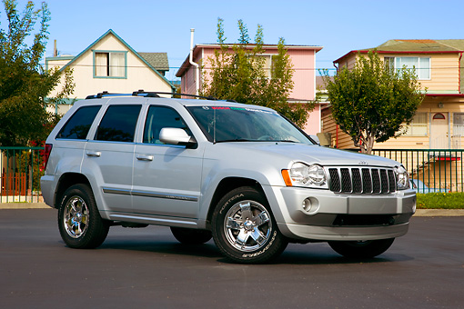 AUT 42 RK0267 01 © Kimball Stock 2007 Jeep Grand Cherokee Overland Silver 3/4 Front View On Pavement By Houses Trees Blue Sky
