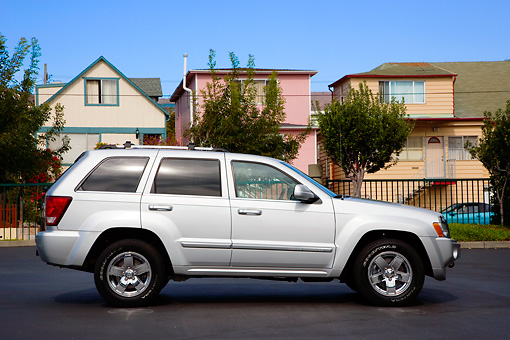 AUT 42 RK0269 01 © Kimball Stock 2007 Jeep Grand Cherokee Overland Silver Profile View On Pavement By Houses Trees Blue Sky