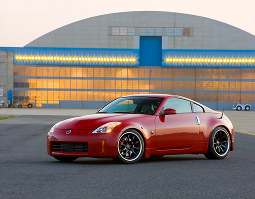 AUT 42 RK0275 01 © Kimball Stock 2007 Nissan 350Z Red 3/4 Front View On Pavement By Hangar