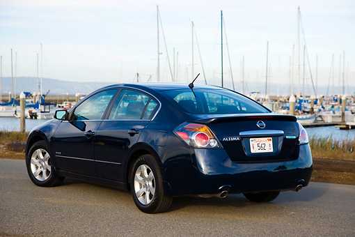AUT 43 RK0084 01 © Kimball Stock 2008 Nissan Altima Hybrid Dark Blue 3/4 Rear View On Pavement By Marina Sky