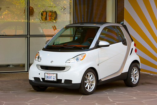 AUT 43 RK0109 01 © Kimball Stock 2008 Smart Fortwo White 3/4 Front View On Pavement By Building