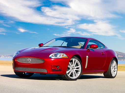 AUT 43 RK0115 01 © Kimball Stock 2008 Jaguar XKR Coupe Red 3/4 Front View On Pavement By Water Blue Sky