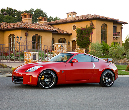 AUT 43 RK0316 01 © Kimball Stock 2008 Nissan 350Z Red 3/4 Front View On Pavement By House