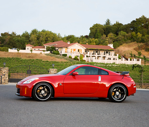 AUT 43 RK0317 01 © Kimball Stock 2008 Nissan 350Z Red Profile View On Pavement By House