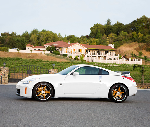 AUT 43 RK0325 01 © Kimball Stock 2008 Nissan 350Z White Profile View On Pavement By House