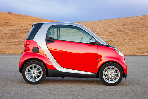 AUT 44 RK0086 01 © Kimball Stock 2009 Smart Fortwo Passion Coupe Red And Silver Profile View On Pavement By Hills