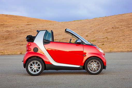 AUT 44 RK0092 01 © Kimball Stock 2009 Smart Fortwo Passion Cabriolet Red And Silver Profile View On Pavement By Hills