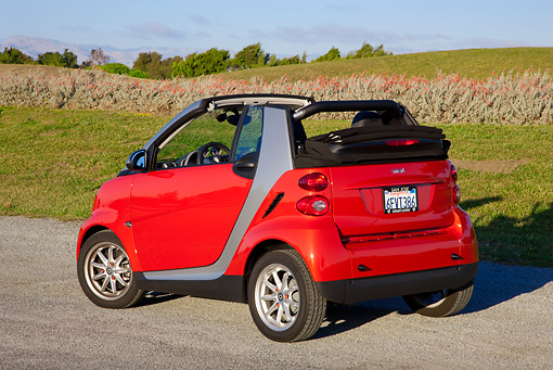 AUT 44 RK0095 01 © Kimball Stock 2009 Smart Fortwo Passion Cabriolet Red And Silver 3/4 Rear View On Pavement By Field