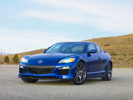 AUT 44 RK0023 01 © Kimball Stock 2009 Mazda RX-8 R3 Coupe Blue 3/4 Front View On Pavement By Hills