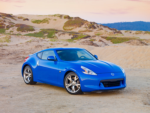 AUT 45 RK0014 01 © Kimball Stock 2010 Nissan 370Z Touring Blue 3/4 Front View On Beach