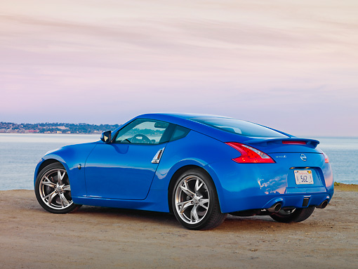AUT 45 RK0020 01 © Kimball Stock 2010 Nissan 370Z Touring Blue 3/4 Rear View On Beach