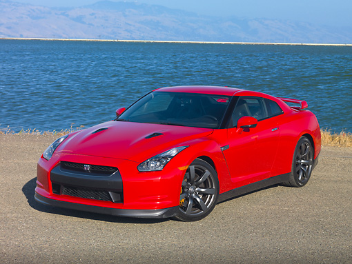 AUT 45 RK0044 01 © Kimball Stock 2010 Nissan GT-R Red 3/4 Front View On Pavement By Water