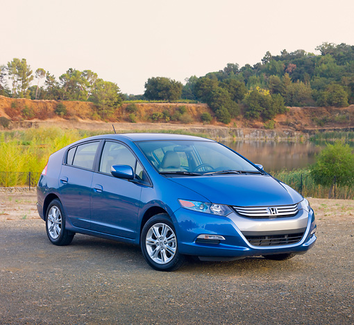 AUT 45 RK0049 01 © Kimball Stock 2010 Honda Insight Blue 3/4 Front View On Pavement By Lake