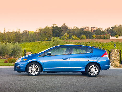 AUT 45 RK0051 01 © Kimball Stock 2010 Honda Insight Blue Profile View On Pavement By Fence