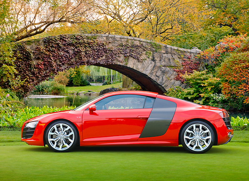 AUT 45 RK0066 01 © Kimball Stock 2010 Audi R8 5.2 FSI Quattro Red Profile View On Grass By Bridge