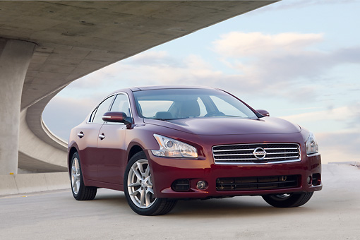 AUT 46 BK0005 01 © Kimball Stock 2011 Nissan Maxima 3.5 SV Premium Red 3/4 Front View On Pavement Under Overpass