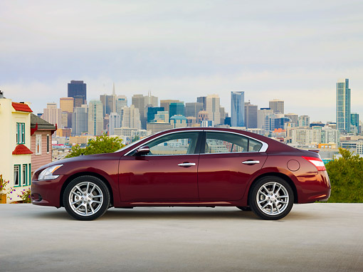 AUT 46 BK0006 01 © Kimball Stock 2011 Nissan Maxima 3.5 SV Premium Red Profile View On Pavement By City Skyline