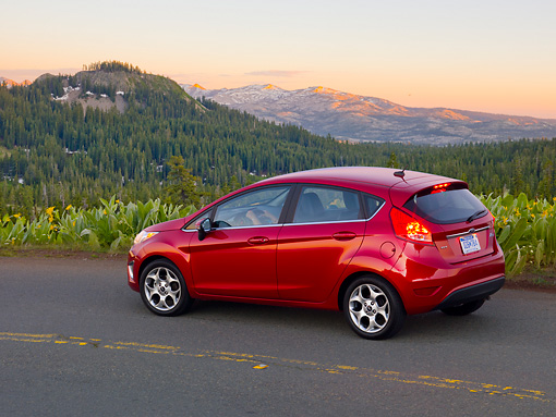 AUT 46 BK0016 01 © Kimball Stock 2011 Ford Fiesta Red 3/4 Rear View On Road By Mountains At Dusk