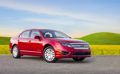 AUT 46 BK0045 01 © Kimball Stock 2011 Ford Fusion Hybrid Red 3/4 Front View On Pavement By Field Of Wildflowers