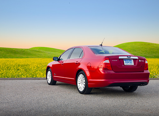AUT 46 BK0047 01 © Kimball Stock 2011 Ford Fusion Hybrid Red 3/4 Rear View On Pavement By Field Of Wildflowers