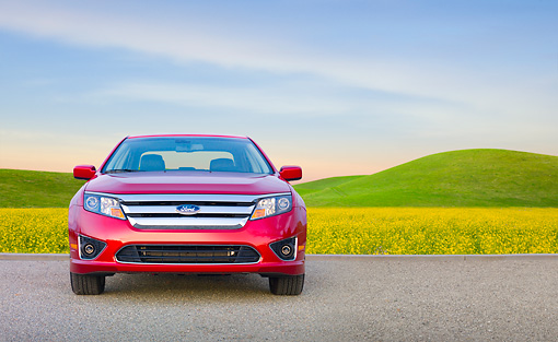 AUT 46 BK0048 01 © Kimball Stock 2011 Ford Fusion Hybrid Red Front View On Pavement By Field Of Wildflowers