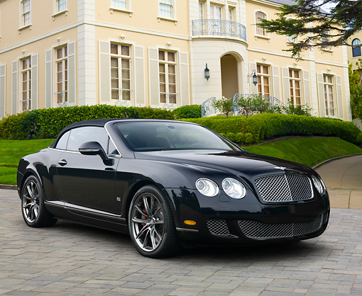 AUT 46 RK0016 01 © Kimball Stock 2011 Bentley Continental GTC Speed 80-11 Edition Black 3/4 Front View On Grass By Building