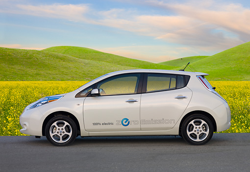 AUT 48 BK0007 01 © Kimball Stock 2012 Nissan Leaf White Profile View On Pavement By Grassy Hills