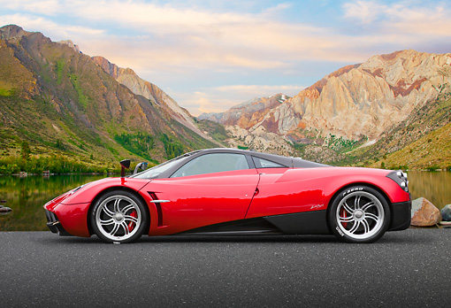 AUT 48 BK0014 01 © Kimball Stock 2012 Pagani Huayra Red Profile View On Pavement By Pond And Mountains