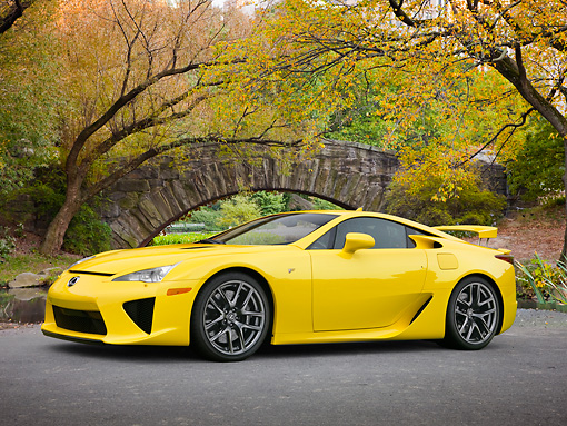 AUT 48 RK0001 01 © Kimball Stock 2012 Lexus LFA Coupe Yellow 3/4 Side View On Pavement By Autumn Trees And Stone Bridge