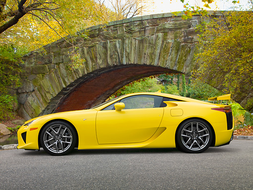 AUT 48 RK0019 01 © Kimball Stock 2012 Lexus LFA Coupe Yellow Profile View On Pavement By Trees And Stone Bridge