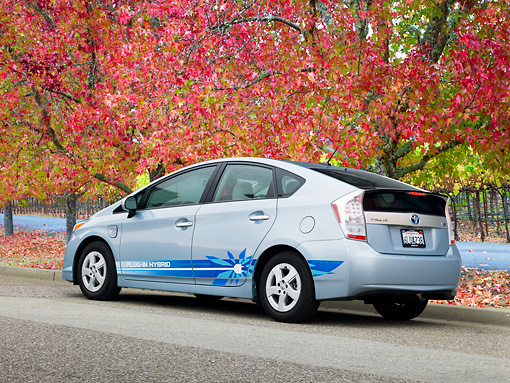 AUT 48 RK0022 01 © Kimball Stock 2012 Toyota Prius Plug-In Hybrid Blue 3/4 Rear View On Pavement By Autumn Trees