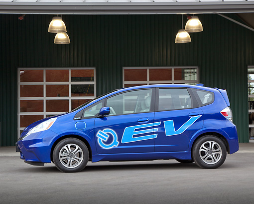AUT 48 RK0062 01 © Kimball Stock 2012 Honda Fit EV Blue Profile View On Pavement By Building
