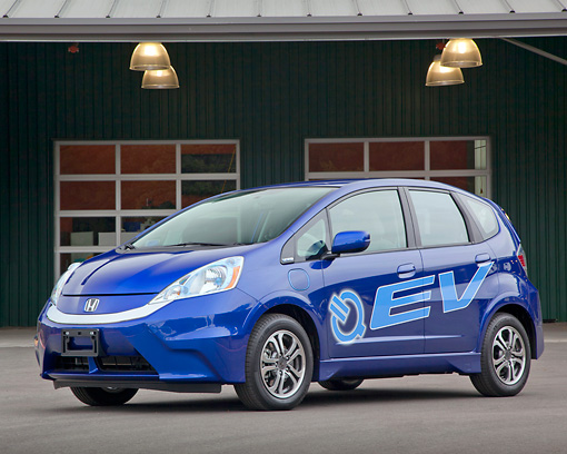 AUT 48 RK0063 01 © Kimball Stock 2012 Honda Fit EV Blue 3/4 Front View On Pavement By Building